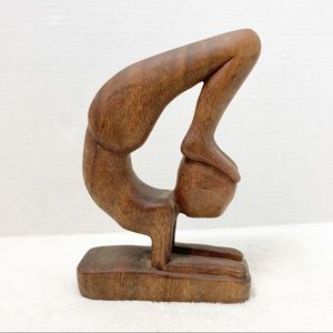 Carved wooden person statue yoga pose